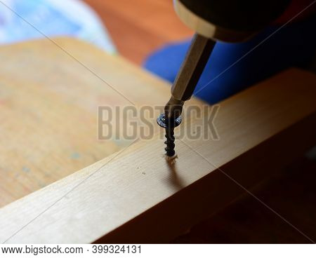 The Black Self-tapping Screw Is Screwed In With An Electric Screwdriver. Home Renovation Concept