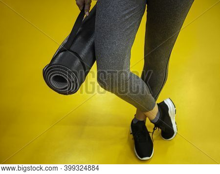 Female Legs In A Sports Ultimate Gray Suit In Hand Hold Mat On Illuminating Yellow Sport Floor, Read