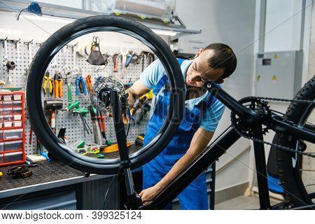 Bicycle repair in workshop, man setting up brake