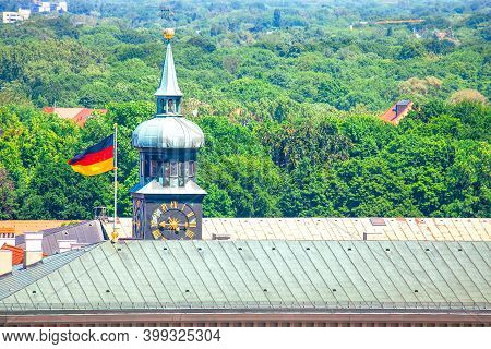 Steeple With Horology Near German Flag On The Roof