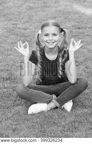 Connecting To Your Higher Self. Happy Child Keep Hands In Mudra. Little Girl Meditate On Green Grass