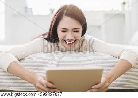 Smiling Young Woman Looking Tablet On  Bed