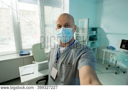 Bald mature male clinician in protective mask looking at you while making selfie in front of camera against his workplace in medical office