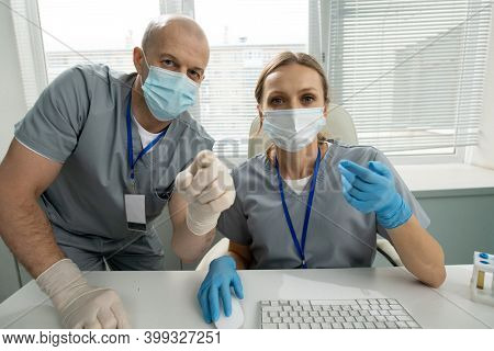 Two contemporary clinicians in protective workwear looking at computer screen while mature man pointing at it and making presentation