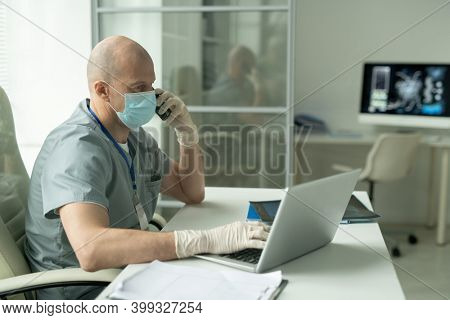 Side view of bald mature male clinician in protective mask sitting by desk in front of laptop in medical office and talking on mobile phone