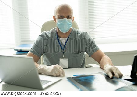 Bald mature male clinician in protective mask looking at you while sitting by workplace in front of camera and using laptop in medical office