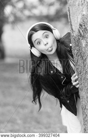 Make Childhood Playful. Playful Girl Stick Tongue At Tree. Little Child Grimace Outdoors. Playful Gr