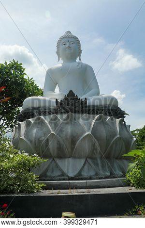 The White Buddha Status On White Lotus. Giant Buddha Image In Bali With Dramatic Sky Background. The
