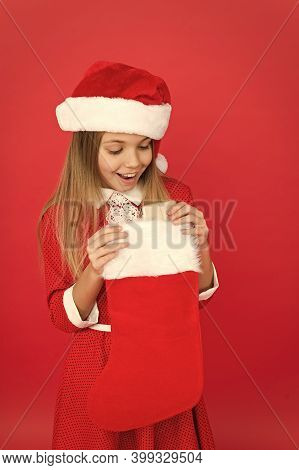 Surprise Inside. Surprised Child Hold Stocking. Little Girl Open Stocking Stuffed With Present. Red