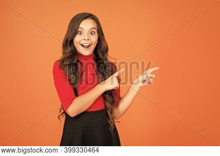 Wow. Surprised Girl Point At Brown Background. Little Child Advertising With Open Mouth. Advertising