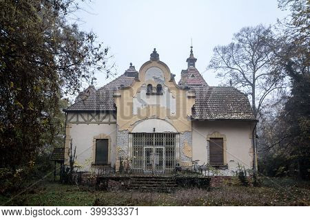 Old And Mysterious Abandoned House, A Former Mansion And Manor, Standing At Dusk In The Middle Of Th