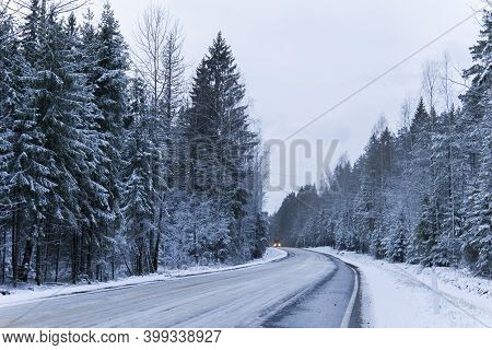 Car Drives On Empty Snowy Road In Winter Forest. Beautiful Frosty White Landscape At Dawn.