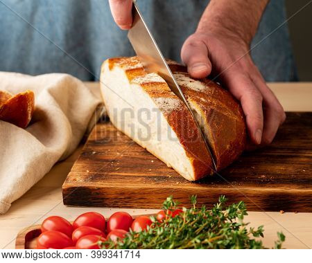 Faceless Man Cutting Fresh Home-baked Crusty Bread With Large Knife On Wooden Board On Kitchen Table