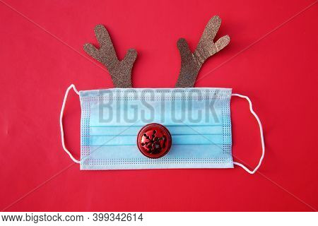 Coronavirus Christmas. Festive Christmas reindeer made from face mask and decorations. Medical Paper Face Mask to avoid contacting Covid-19 with Deer Antlers and a Bell for a Nose. Covid-19 Christmas