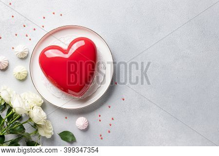 Frame Made Of Rose Flowers, Heart Shape Mousse Cake And Sweets On Gray Background. Valentines Day Co