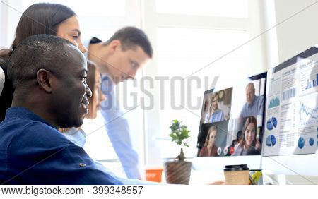 Group Of Businesspeople Having Video Conference With Another Business Team In Office, Discussing Fin