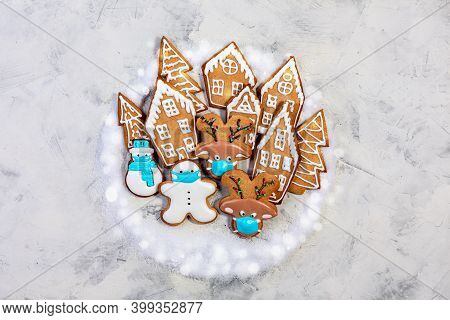 Funny Ginger Cookies In Protective Masks Among Gingerbread Houses And Fir Trees. Concept Of Winter A