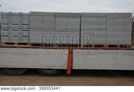 Transport Of Concrete Bricks With For House Foundations Or Fencing. Pallets With Gray Bricks Are Unl