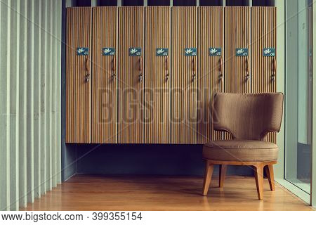 Locker Room With Brown Chair And Wooden Lockers In The Gym.