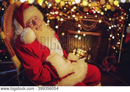 Cheerful Santa Claus is swinging on a rocking chair in a room with a beautiful Christmas interior. Christmas and New Year celebration.