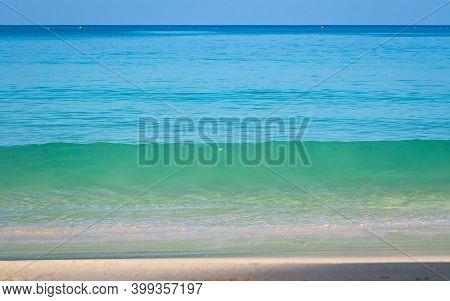 Breaking Sea Wave On A Sandy Beach Background