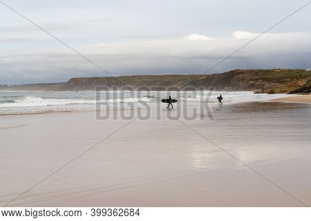 Baleal, Beira Litoral - Portugal - 13 December 2020: Surfer And Body Boarder Head Into The Water For