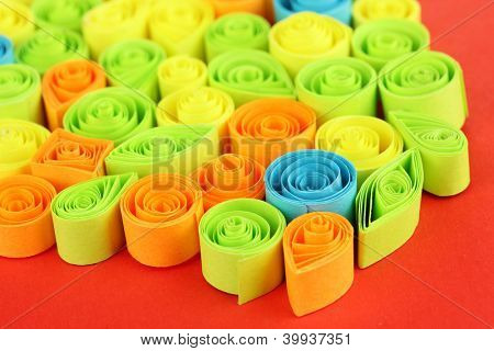 Colorful quilling on red background close-up poster