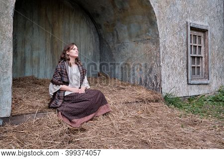 Woman In Vintage Dress Sitting In The Hayloft - Retro Shawl, Shirt And Dress