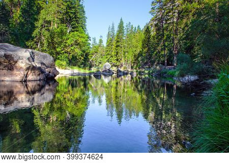 The shady forest is reflected in the smooth water. Charming little lake in the Yosemite Valley. Yosemite Park is located on the slopes of the Sierra Nevada