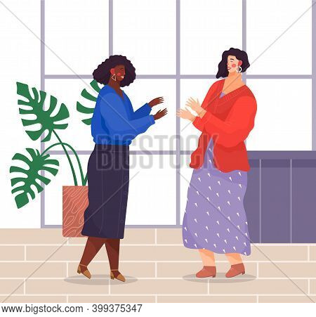 Two Women Standing And Talking In Office. Dark-skinned Girl Wears Jewelry, Blue Blouse, Denim Skirt,