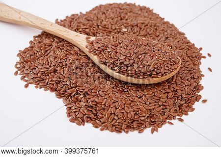 Flax Seeds On A White Background Close-up Of Flax Seeds In A Wooden Spoon.selectiv Focus