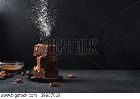 Stack Of  Brownies On Black Background. Delicious Homemade Chocolate Dessert, Brownie With Sugar Pow