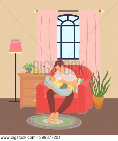 Young Father Feeding His Baby Son With Milk From Bottle. Dad Sitting In Armchair In Room And Holding