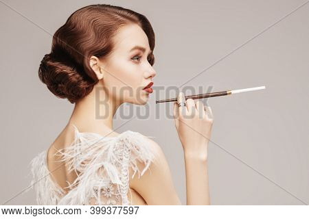 Beautiful chic woman in a luxury white dress smoking a cigarette in the mouthpiece. Evening makeup and hairstyle of the 20s. Hollywood style.
