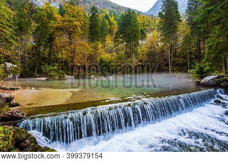 Autumn forest in a mountain valley. Picturesque shallow lake with glacial greenish water. Artificial waterfall - dam. Light fog rises above the water. Julian Alps, Slovenia