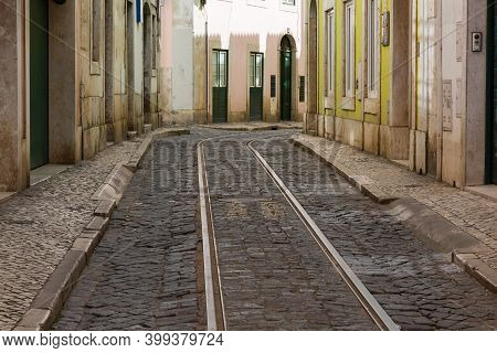 Empty Narrow Cobblestone Street Or Alley With Tramway Rails, Lisbon, Portugal