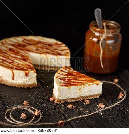Cheesecake With Caramel Sauce On Black Background. Tasty Homemade Caramel Cheesecake