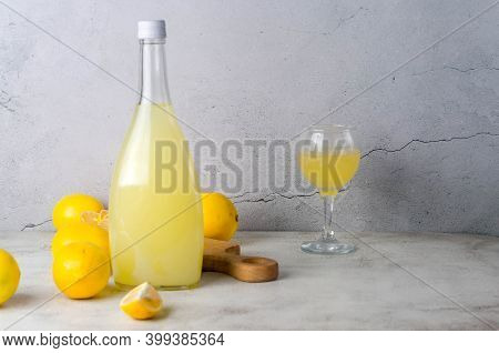 Limoncello In Glass Bottle And Fresh Ripe Yellow Lemons On The Grey Background, Traditional Homemade