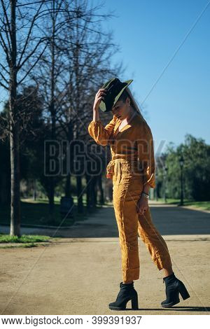 Young Gorgeous Woman In Bright Overalls Wearing Hat Sensually Posing On Camera In Park. Posh Model O