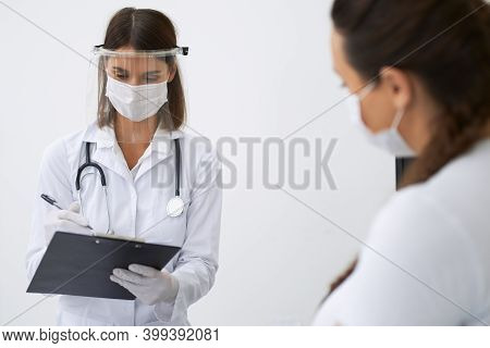 Female Doctor Providing Health Care Treatment For Pregnant Woman At Modern Clinic. Gynecologist And