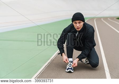 Young man runner tying shoelaces at the stadium