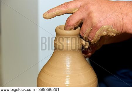 Hands Of A Potter. Potter Making Ceramic Vase On The Pottery Wheel.\n\ncreating A Vase Of Clay Close
