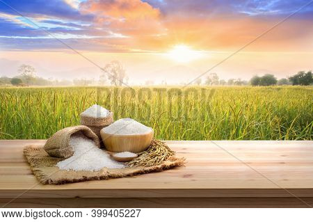 Asian Uncooked White Rice With The Sunset Rice Field Background And Burlap Sack On Wooden Table. Ric