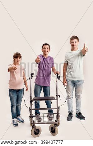 Full Length Shot Of Three Disabled Children With Down Syndrome And Cerebral Palsy Smiling, Showing T