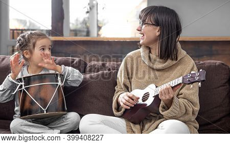 Mom Plays With Her Daughter At Home. Lessons On A Musical Instrument. Children's Development And Fam