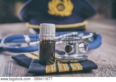 Close up of an airplane pilot equipment hat and epaluetes with doctor's stethoscope, forms, medical and pilot certificate and drugs. Conceptual image of medical exam.