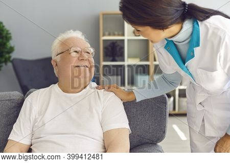 Friendly Doctor Visiting Happy Senior Man At Home For Check-up, Supporting Him And Cheering Him Up