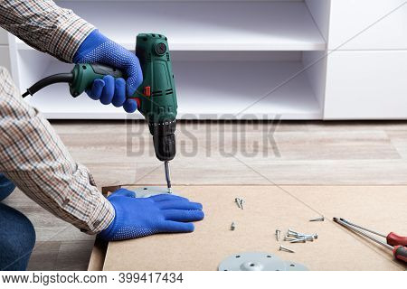 Man In Gloves Assembles Table Furniture With Drill. Assembly, Furniture Repair Home Master. Male Han