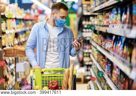 Buying Food. Portrait Of Young Man Wearing Medical Face Mask Shopping Groceries In Hypermarket, Stan