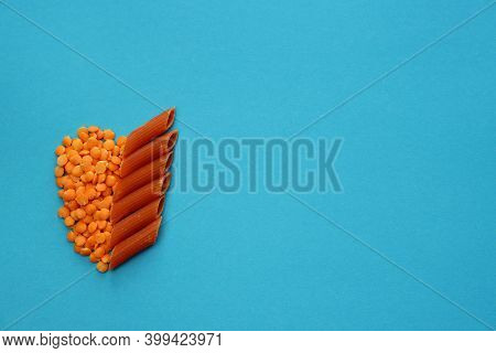 Red Lentils And Red Penne Pasta On A Blue Background. Red Lentil Penne Paste.